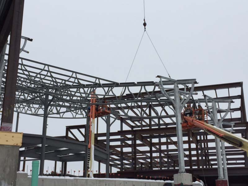 crane putting up Steel trusses during construction