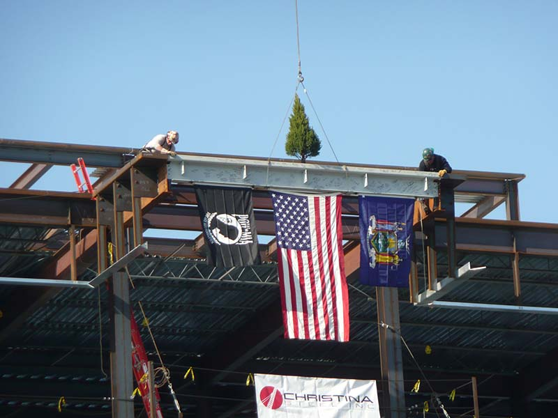 flags and tree at top of steel frame building during construction